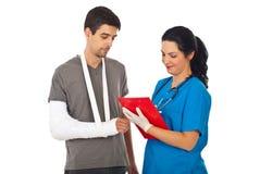 Il medico dà la prescrizione all'uomo ferito Fotografie Stock Libere da Diritti