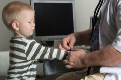 Il medico del bambino esamina i pazienti nel suo ufficio I bambini felici sono molto affettuosi di buon pediatra Il concetto di u Immagini Stock Libere da Diritti