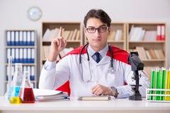Il medico del supereroe che lavora in laboratorio l'ospedale Fotografia Stock