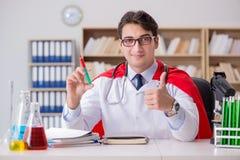 Il medico del supereroe che lavora in laboratorio l'ospedale Immagini Stock Libere da Diritti