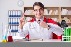 Il medico del supereroe che lavora in laboratorio l'ospedale Fotografia Stock Libera da Diritti