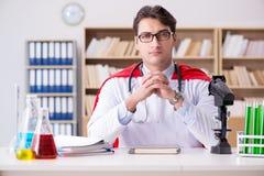 Il medico del supereroe che lavora in laboratorio l'ospedale Immagini Stock