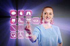 Il medico della donna che preme i bottoni con le varie icone mediche Fotografie Stock Libere da Diritti
