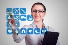 Il medico della donna che preme i bottoni con le varie icone mediche Immagini Stock