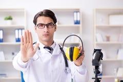 Il medico di sicurezza che consiglia circa il rumore che annulla le cuffie Immagini Stock