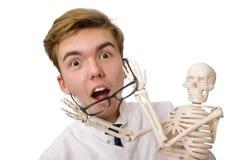 Il medico divertente con lo scheletro isolato su bianco Immagine Stock