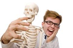 Il medico divertente con lo scheletro su bianco Immagine Stock