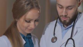 Il medico e due giovani internano esaminando la compressa e discutono i risultati dell'indagine paziente video d archivio