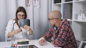 Il medico esamina i raggi x del braccio del paziente Un paziente con un polso bendato che si siede nell'ambulatorio stock footage