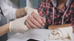Il medico esamina i raggi x del polso nocivo del paziente Il medico esamina il braccio del paziente Medico ispeziona archivi video