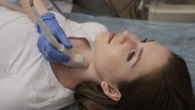 Il medico esamina il suo collo paziente del ` s con un dispositivo di ultrasuono video d archivio