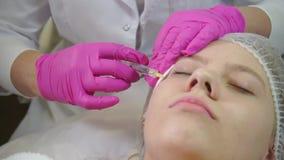 Il medico fa un'iniezione nel fronte della ragazza video d archivio