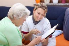 Il medico femminile fa un controllo Fotografie Stock Libere da Diritti
