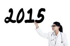 Il medico femminile scrive il numero 2015 sulla lavagna Immagini Stock
