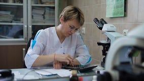 Il medico nel suo ufficio riempie la prescrizione o l'anamnesi Una donna di mezza età con i vetri, carta intorno video d archivio