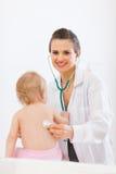 Il medico pediatrico esamina il bambino che per mezzo dello stetoscopio Fotografie Stock