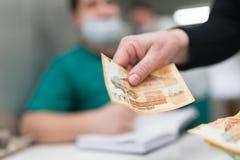 Il medico prende i soldi dal paziente Fotografia Stock Libera da Diritti