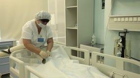 Il medico prepara il dispositivo per il riscaldamento del paziente dopo l'operazione archivi video