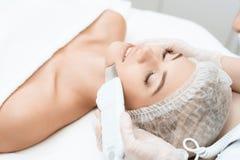 Il medico pulisce la pelle del ` s della donna con un apparecchio medico speciale La donna è venuto alla procedura di depilazione fotografie stock libere da diritti