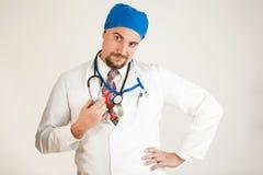 Il medico sorride in dubbio, lui tiene lo stetoscopio con la sua mano fotografia stock