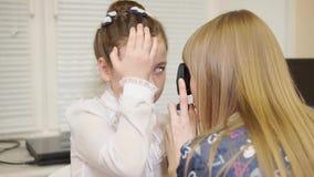 Il medico splende nell'allievo della ragazza, il bambino vuole riparare la vista stock footage