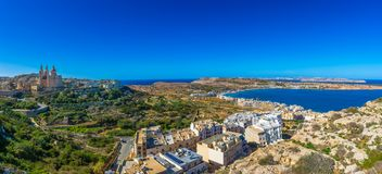 Il-Mellieha, Malta - Beautiful panoramic skyline view of Mellieha beach and Mellieha town. On a bright summer day with Paris Church, Agatha Red Tower and island Stock Photos