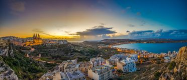 Il-Mellieha, Malta - Beautiful panoramic skyline view of Mellieha town at sunset with Paris Church. And Mellieha beach at background with blue sky and clouds Royalty Free Stock Photo