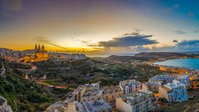 Il-Mellieha, Malta - Beautiful panoramic skyline view of Mellieha town at sunset with Paris Church. And Mellieha beach at background with blue sky and clouds Royalty Free Stock Images