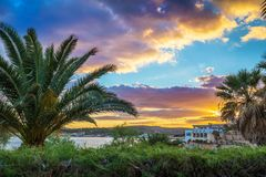 Il-Mellieha, Malta - Beautiful sunset scene at Mellieha beach with palm trees. And colorful sky Royalty Free Stock Images