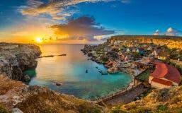 IL-Mellieha, Malta - opinión panorámica del horizonte del pueblo famoso de Popeye en la bahía del ancla en la puesta del sol fotos de archivo