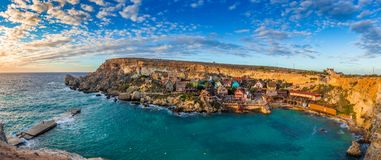 Il-Mellieha, Malta - Panoramic skyline view of the famous Popeye Village at Anchor Bay. At sunset with amazing cluds and sky Stock Photography