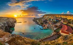 Il-Mellieha, Malta - Panoramic skyline view of the famous Popeye Village at Anchor Bay at sunset. With traditional Luzzu boats, beautiful colorful clouds and Stock Photos