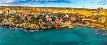 Il-Mellieha, Malta - Panoramic view of the famous Popeye Village at Anchor Bay at sunset. This village was the set in Robert Altman`s famous movie `Popeye` Stock Photo