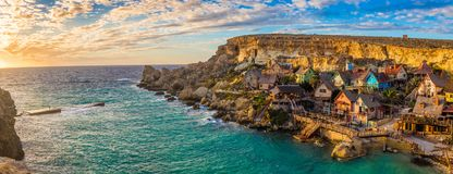 IL-Mellieha, Malta - panoramische Skylineansicht des berühmten Popeye-Dorfs an der Anker-Bucht bei Sonnenuntergang lizenzfreie stockbilder