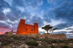 Il-Mellieha, Malta - St Agatha`s Red Tower at blue hour with tree and beautiful clouds royalty free stock photography