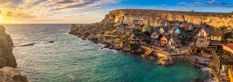Il-Mellieha, Malta - Sunset at the famous Popeye Village at Anchor Bay. On a panoramic image Royalty Free Stock Photos