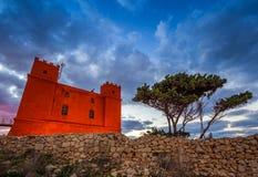 IL-Mellieha, Malta - torre vermelha do ` s do St Agatha na hora azul com árvore e as nuvens bonitas Imagens de Stock