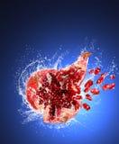 Il melograno incrinato con i semi in acqua spruzza Fotografia Stock
