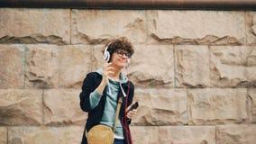 Il melomaniac felice della giovane donna è cantante e ballante ascoltare la musica in cuffie e la tenuta dello smartphone all'ape archivi video