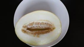 Il melone del taglio si trova su un fondo bianco su una tavola scura stock footage