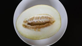 Il melone del taglio si trova su un fondo bianco su una tavola scura archivi video