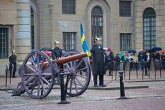 Il membro della guardia reale con un'insegna ad una vecchia pistola dell'artiglieria Cerimonia del divorzio della guardia vicino  Fotografie Stock Libere da Diritti