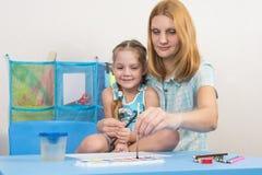 Il mentore e la ragazza di cinque anni disegna l'immagine delle pitture alla tavola nell'asilo fotografia stock