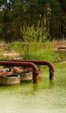 Il metall arrugginito convoglia la conclusione nell'acqua Immagini Stock
