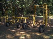 Il metallo del metallo del bilanciere della barra dell'articolo sportivo di sport fatto da sé sotto gli alberi del parco naturale immagine stock