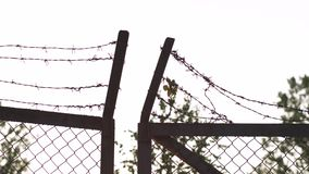 Il metallo del filo spinato recinta il tramonto dorato uguagliante di ora - segno della gabbia del pericolo e di nessuna libertà video d archivio