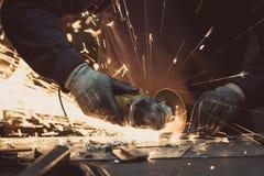 Il metallo di sawing dell'uomo con una smerigliatrice di angolo rotatoria su una superficie di alluminio e sulla generazione scin Immagine Stock