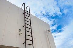 Il metallo industriale verticale della vecchia scala ha arrugginito al serbatoio di acqua Fotografie Stock Libere da Diritti