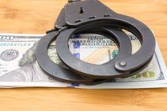 Il metallo nero ammanetta la menzogne sui 100 dollari di banconote Fotografia Stock Libera da Diritti