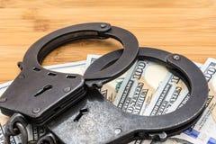 Il metallo nero ammanetta la menzogne sui 100 dollari di banconote Fotografie Stock Libere da Diritti